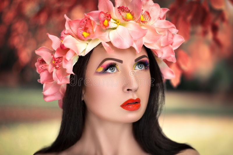 Beautiful Girl in a Flower Wreath. Portrait of a beautiful girl in a flower wreath. brunette woman with bright professional art make up, big eyes, orange lips royalty free stock photos