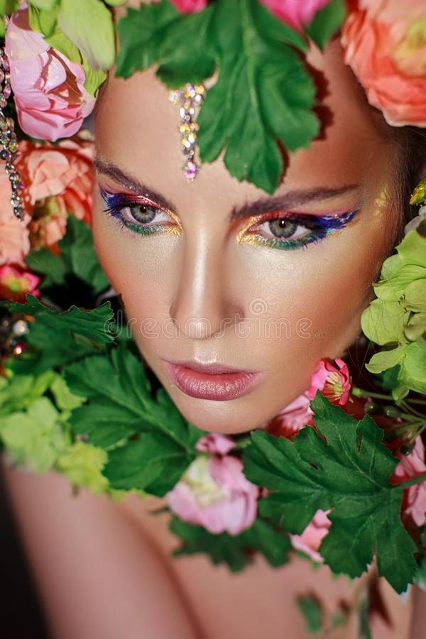 Portrait of a girl in flowers. Portrait of beautiful girl in flowers and leaves on black background. Multi-colored eye makeup royalty free stock photos