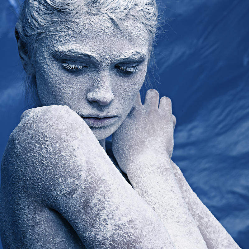 Portrait of a beautiful girl in the frost. On his face on a blue ice background royalty free stock photo