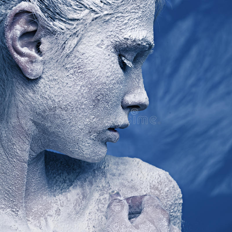Portrait of a beautiful girl in the frost. On his face on a blue ice background stock images