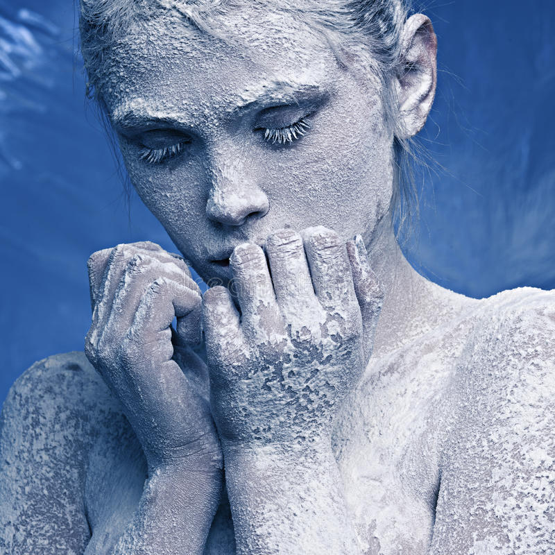 Portrait of a beautiful girl in the frost. On his face on a blue ice background royalty free stock photography