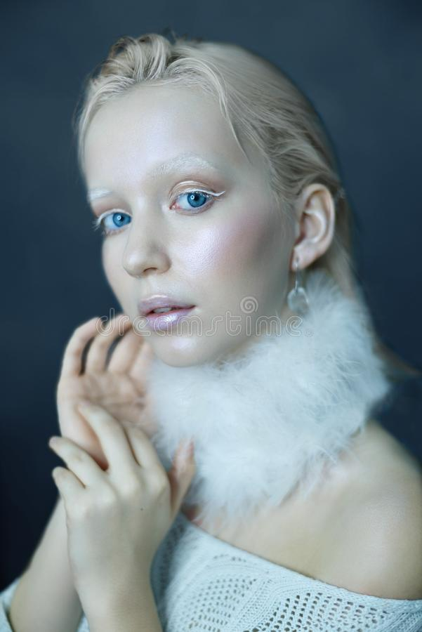 Portrait of a beautiful girl in the frost on his face on a blue ice background royalty free stock photography