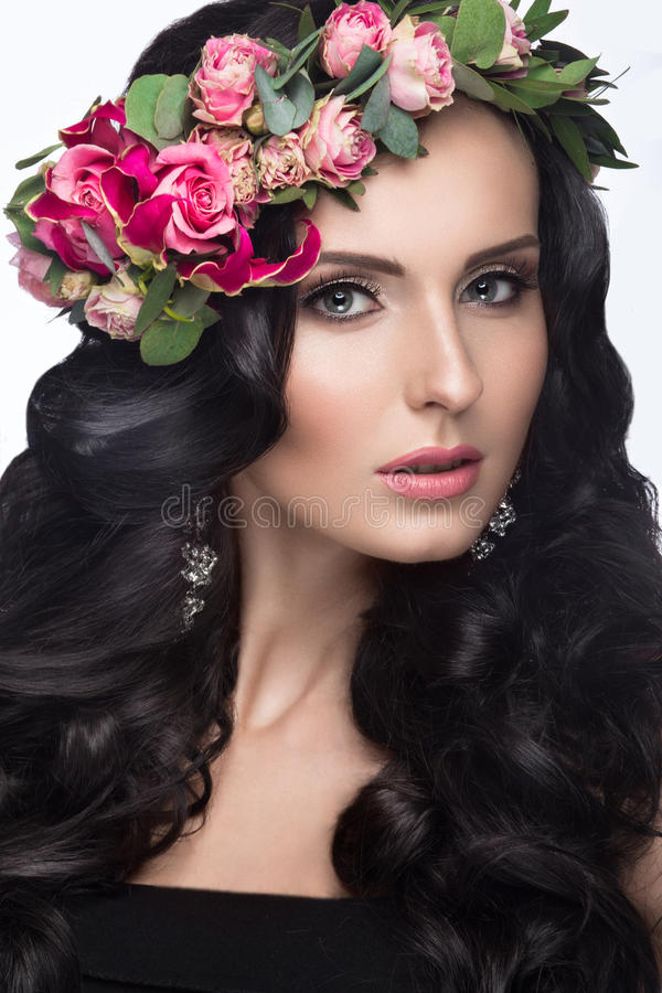 Portrait of a beautiful girl with a gentle make-up and lots of flowers in her hair. Spring image. Beauty face. Picture taken in the studio on a white stock photos