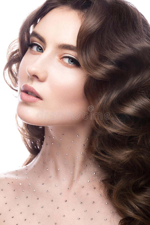Portrait of beautiful girl with a gentle makeup, curls and crystals on the body. beauty face. Portrait of a beautiful girl with a gentle make-up, curls and stock photography