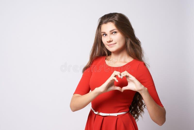 Portrait beautiful girl. Gesture heart. Brunette. Red dress. White background.  stock photos