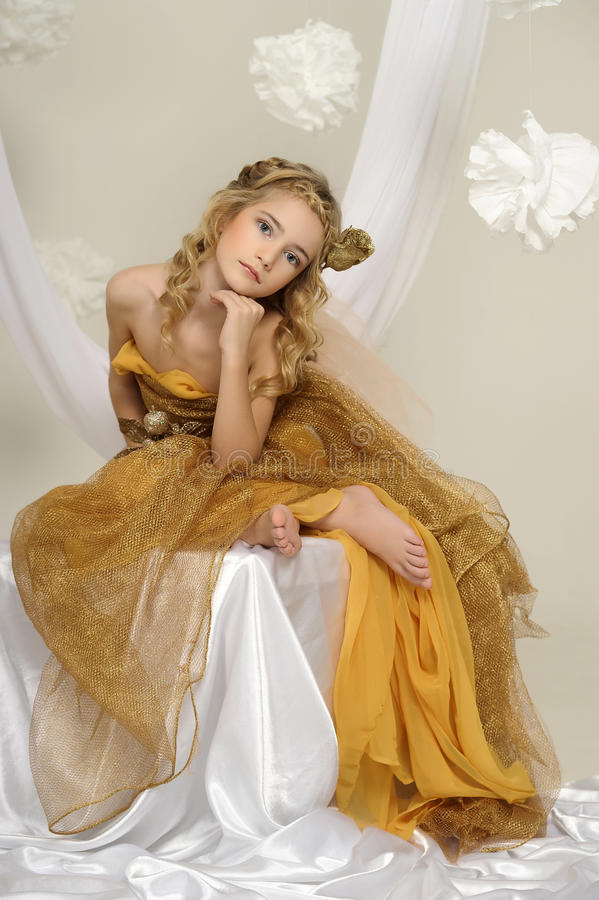 Portrait of a beautiful girl in a gold stock photography
