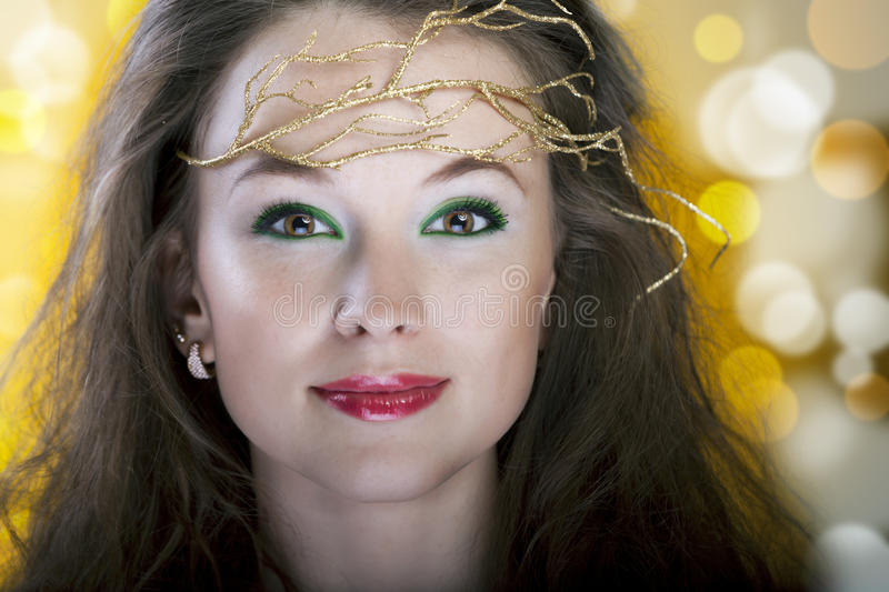 Portrait of beautiful girl with a gold branch in hair with lens royalty free stock images