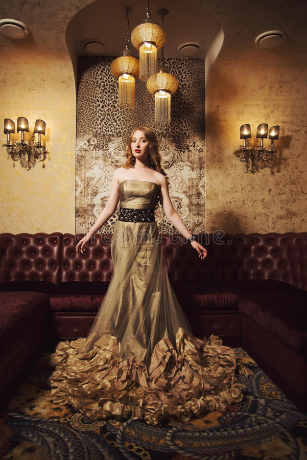 Portrait of a beautiful girl in a gold dress in beautiful interior royalty free stock photo