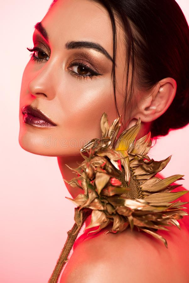 portrait of beautiful girl with golden sunflower red stock photo