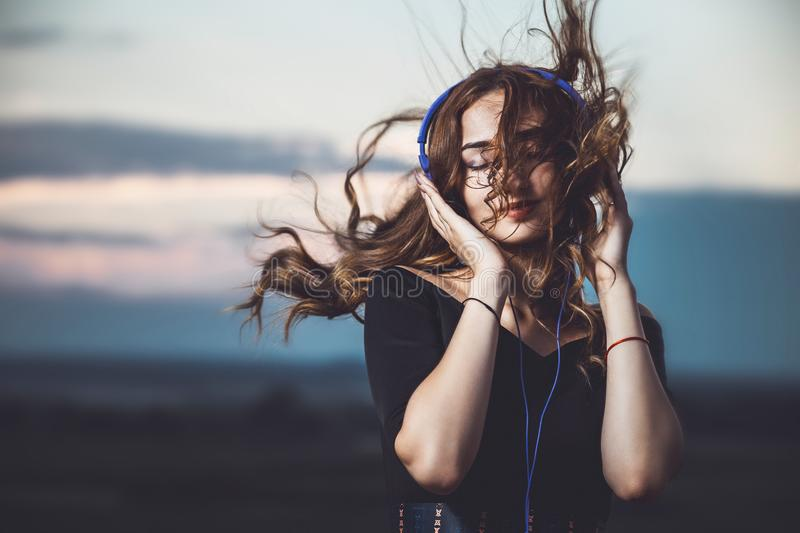 Portrait of a beautiful girl in headphones listening to music on nature. Romantic portrait of a beautiful girl in headphones with flying hair from the wind stock photo