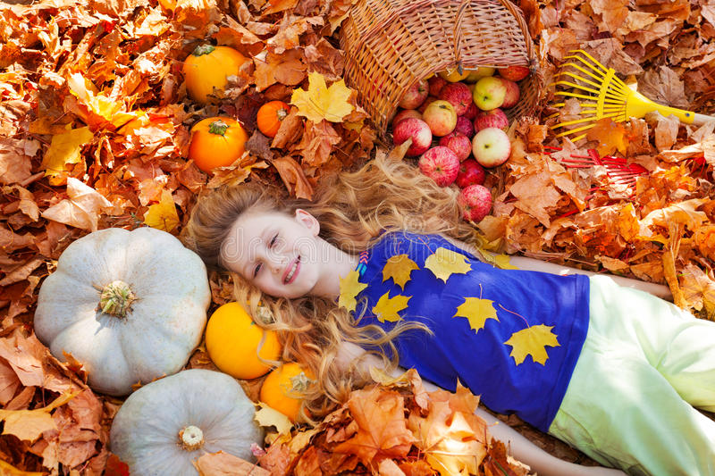 Portrait of beautiful girl on leaves with pumpkins royalty free stock image
