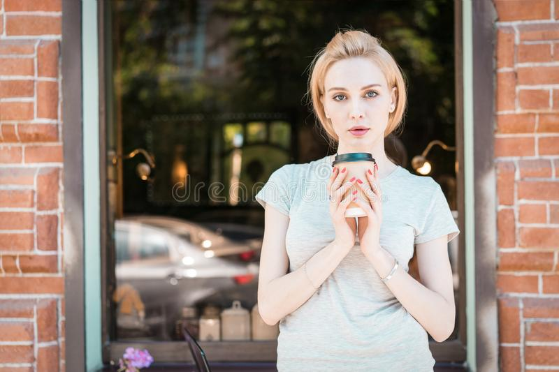 Portrait beautiful girl with long blonde hair holds a coffee cup stands by the window of a street city cafe, looks to camera royalty free stock photography