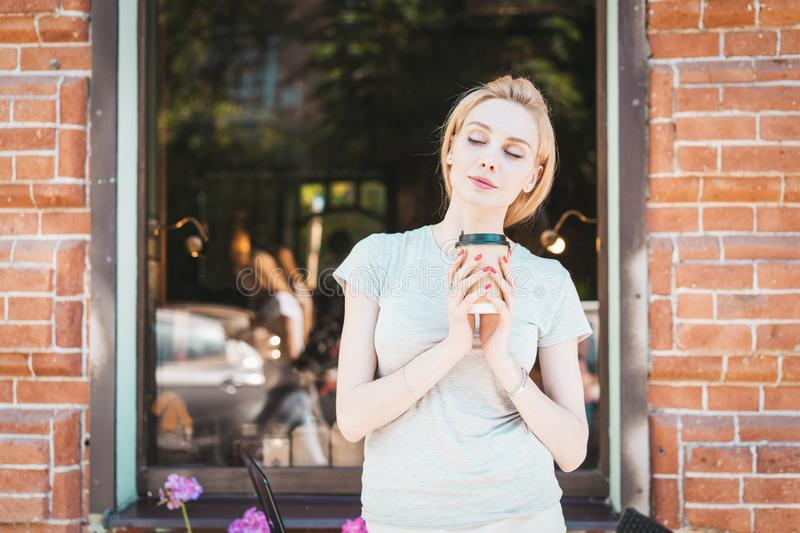 Portrait beautiful girl with long blonde hair relaxing in street with morning coffee royalty free stock images