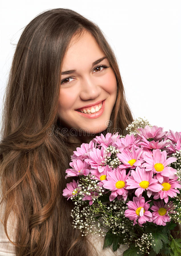 Portrait of a beautiful girl with long hair and a pink flowers. Portrait of a beautiful brunette girl with luxurious long hair and a pink flowers stock photography