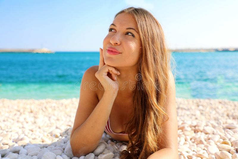Portrait of beautiful girl lying on the beach had an idea for her summer holidays or dreaming about something. Looking to the side stock image