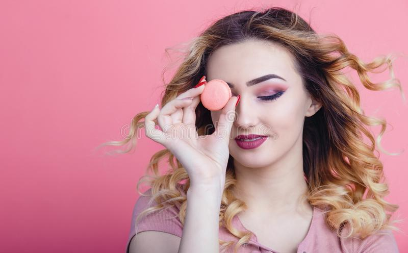 Portrait of a beautiful girl with macaroon in hands on a bright color background, concept of advertising food, diet, sweets royalty free stock image