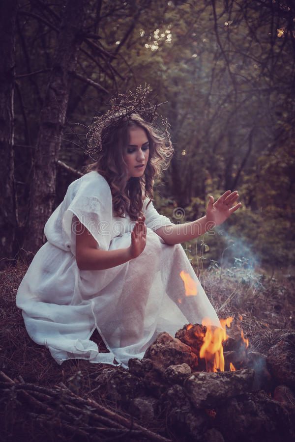 Portrait of beautiful girl with magic eyes. In wreath and dress in the forest outdoor. Bright witch, druid, shaman. book cover stock photos