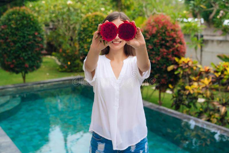 Portrait of beautiful girl makes eyes with two pieces of dragon fruits, pitaya stock photography