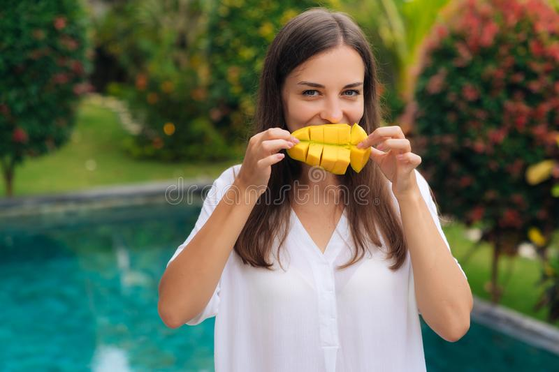Portrait of beautiful girl makes smile with mango pieces royalty free stock image