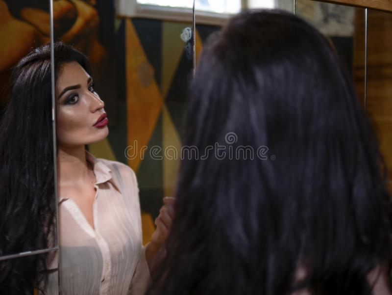 Portrait of a beautiful girl with makeup and beautiful lips looking into a large mirror indoors stock photography