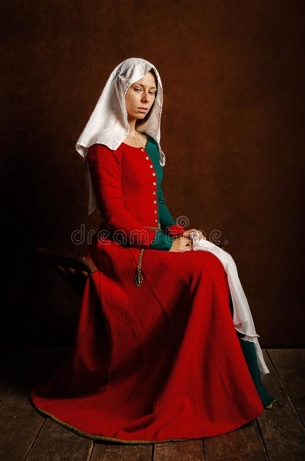Portrait of a beautiful girl in a medieval dress in red and green on a brown background royalty free stock images