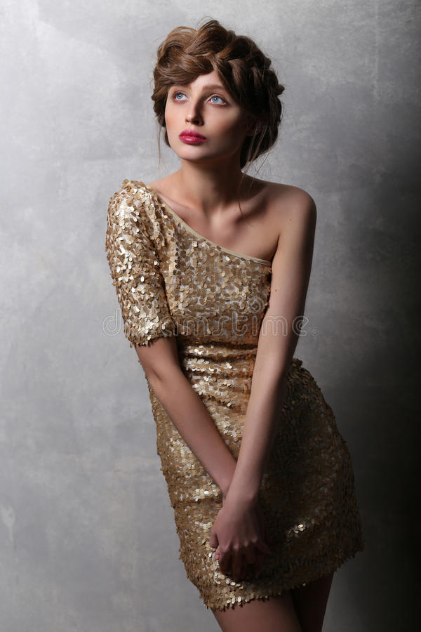 Portrait beautiful girl model in a gold dress. stock images