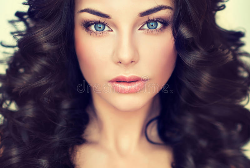 Portrait beautiful girl model with long black curled hair. And bright blue eyes stock photos