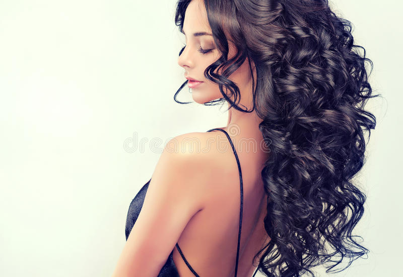 Portrait beautiful girl model with long black curled hair. And bright blue eyes royalty free stock photos