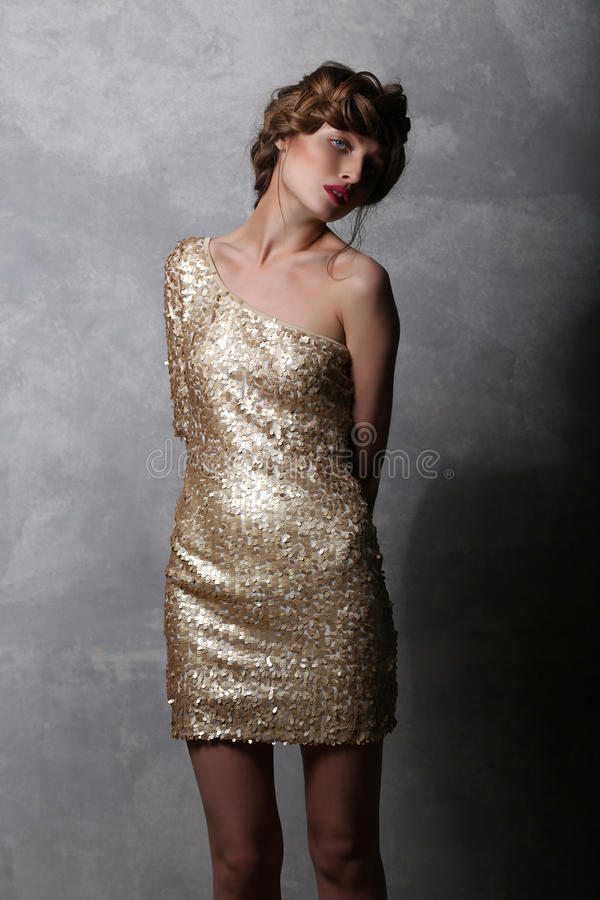 Portrait beautiful girl model in a luxurious gold dress. stock image