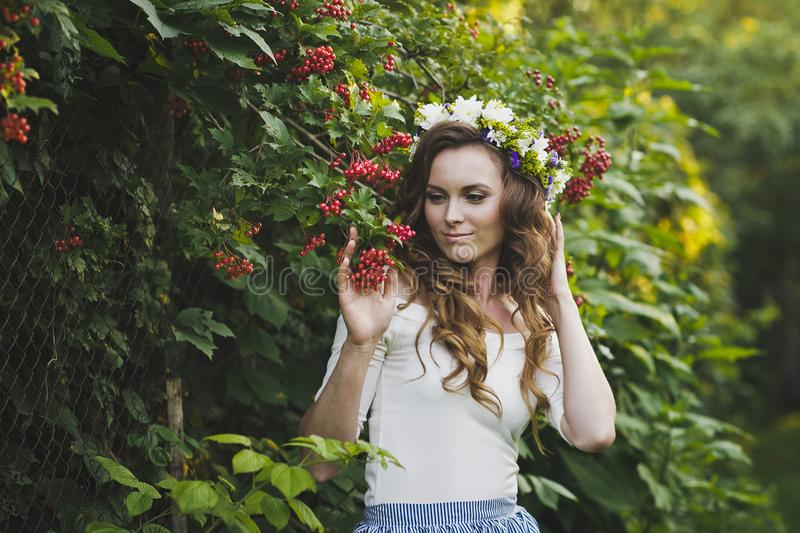 Portrait of a girl with a wreath on his head in the garden 4798. Portrait of a beautiful girl near the Bush of the mountain ash royalty free stock image