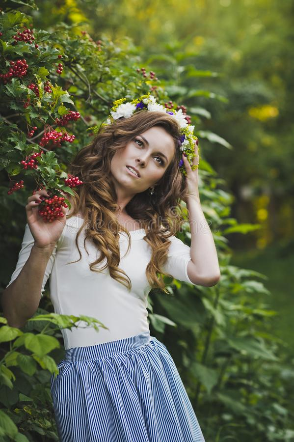 Portrait of beautiful girl near the Bush of the mountain ash 4796. Portrait of a girl with a wreath on his head in the garden royalty free stock photos