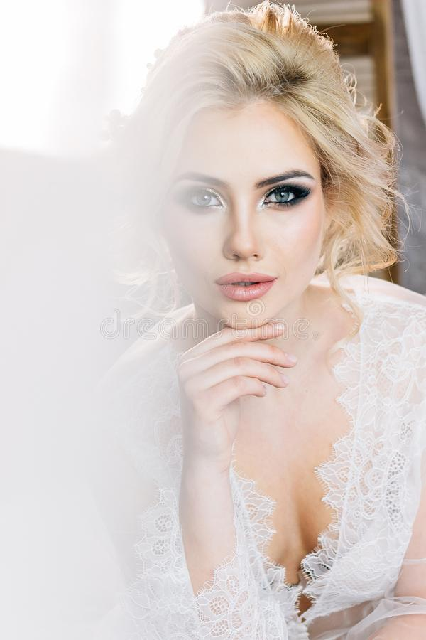 Portrait of a beautiful girl in a negligee with beautiful hair a. Portrait of a beautiful blond girl in a negligee with a beautiful hairdo and makeup royalty free stock images