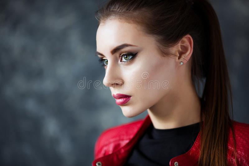 Portrait of beautiful girl with perfect red lips wearing red jacket. royalty free stock photos