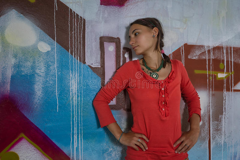 Portrait of beautiful girl posing near a graffitti stock photos