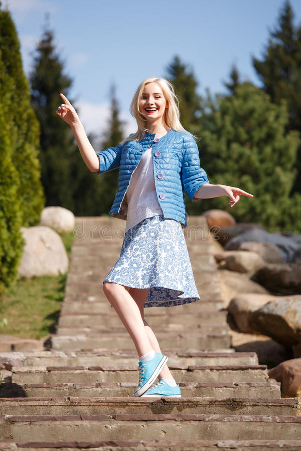 Portrait of beautiful girl posing in the Park. Fashion style skirt jacket royalty free stock images