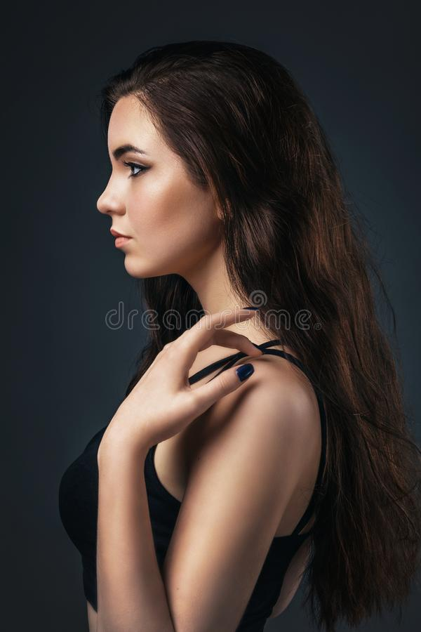 Portrait of a beautiful girl in profile on a homogeneous background. Beautiful smooth skin model royalty free stock photo