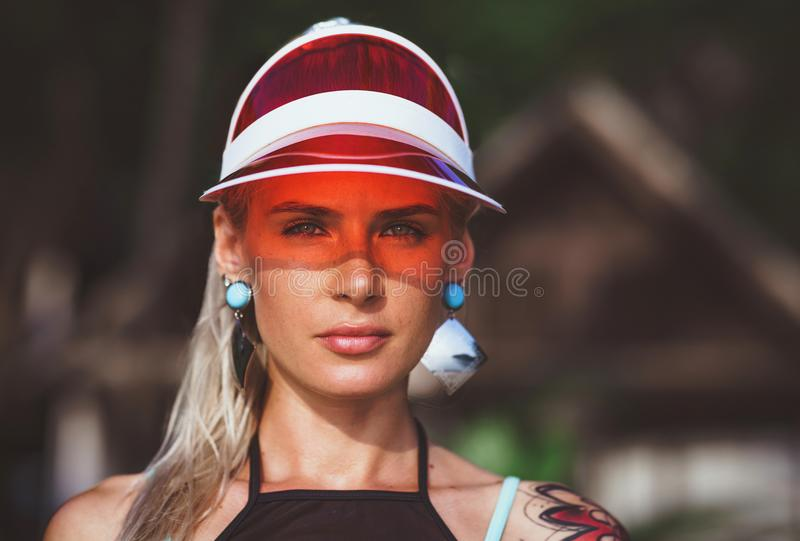 Portrait of a beautiful girl in a red visor closeup. Wearing Large turquoise earrings. Holiday in Thailand.  royalty free stock images