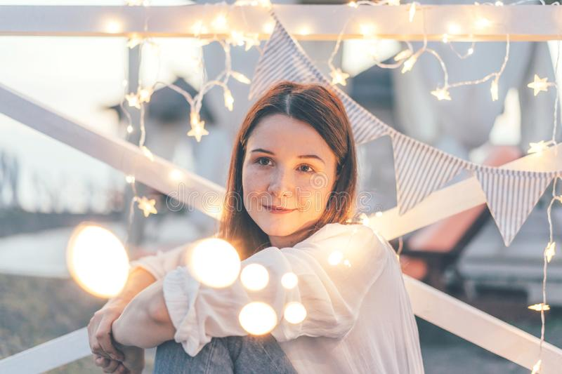 Portrait of a beautiful girl in the shining lights of a garland. A cozy summer holiday, friendly youth party royalty free stock photography