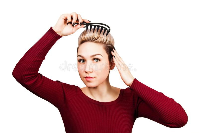 Portrait of beautiful girl with short hairstyle holding comb nad combing hair. Isolated on white background royalty free stock image