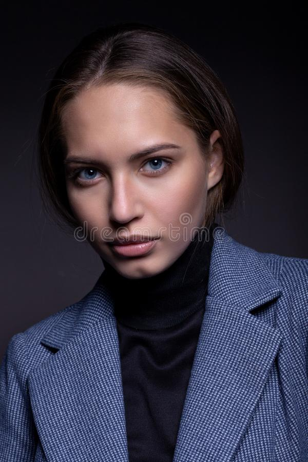 Portrait of a beautiful girl in a simple style in black golf and a coat royalty free stock images