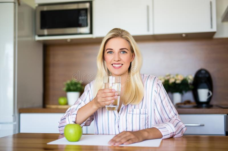 Portrait of beautiful girl sitting with apple and glass of water in kitchen royalty free stock image