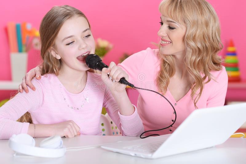 Portrait of beautiful cute girl sitting at table and singing karaoke stock image