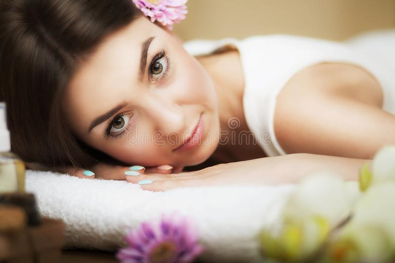 Portrait of a beautiful girl in a spa. Gentle look. Flowers in hair. Aroma oil. Massage cabinet. The concept of health and beauty. stock images