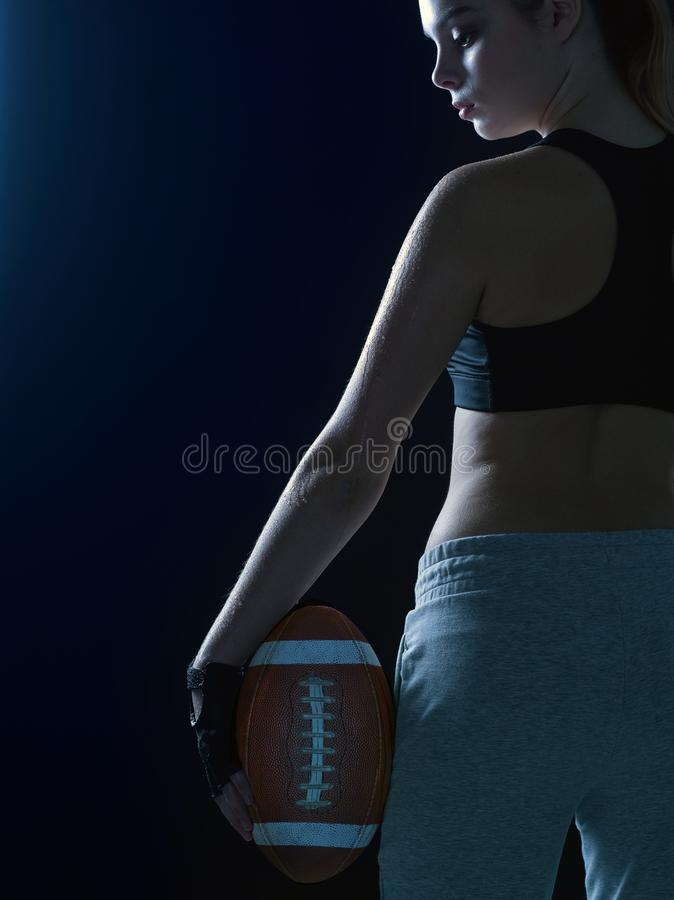 Portrait of a beautiful girl in a sport suit with a ball for American football. stock photo