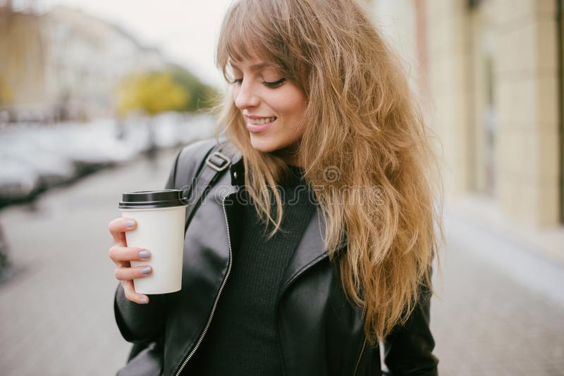 Portrait of a beautiful girl on the street, holding a paper cup royalty free stock images