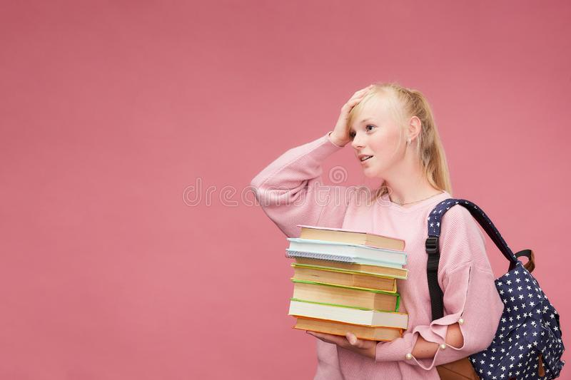 Portrait of a beautiful girl student with a backpack and a stack of books in his hands is smiling at the pink background royalty free stock photo
