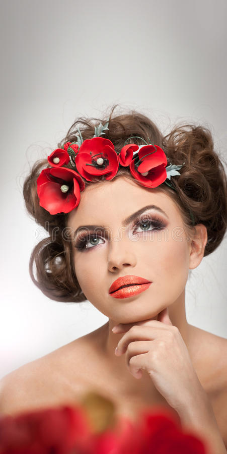 Portrait of beautiful girl in studio with red flowers in her hair and naked shoulders. young woman with professional makeup royalty free stock photos