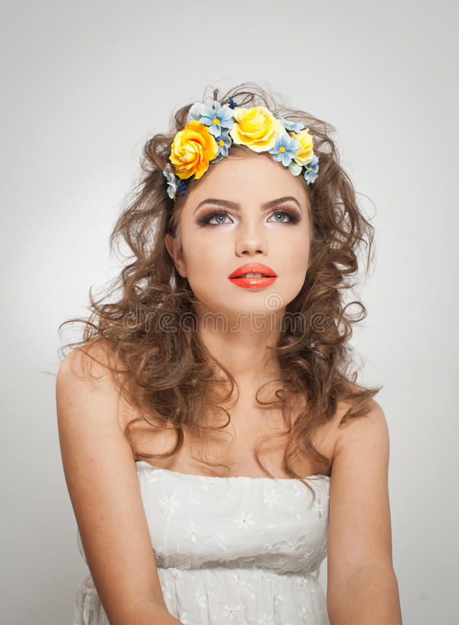 Portrait of beautiful girl in studio with yellow roses in her hair and naked shoulders. young woman with professional makeup stock images
