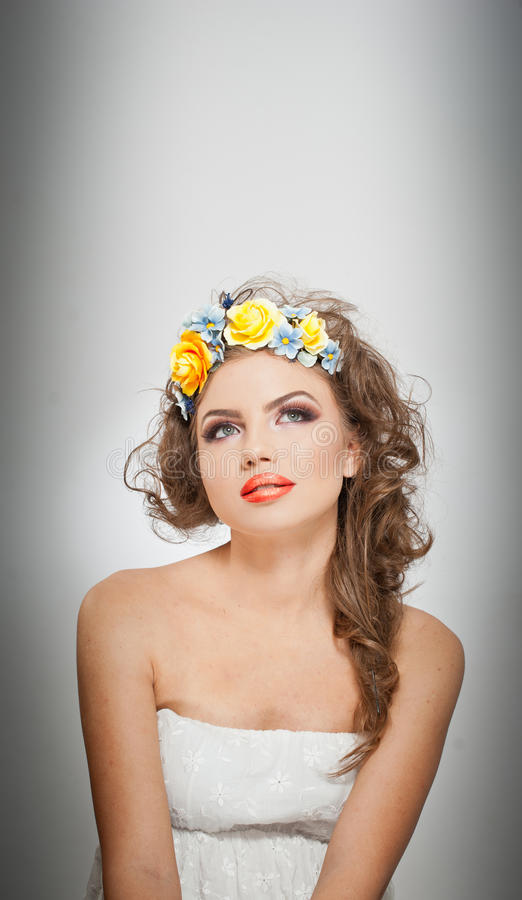 Portrait of beautiful girl in studio with yellow roses in her hair and naked shoulders. young woman with professional makeup stock photo