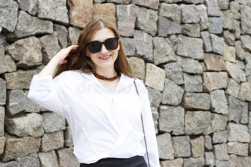 Portrait of beautiful girl in sunglasses on gray concrete background royalty free stock images